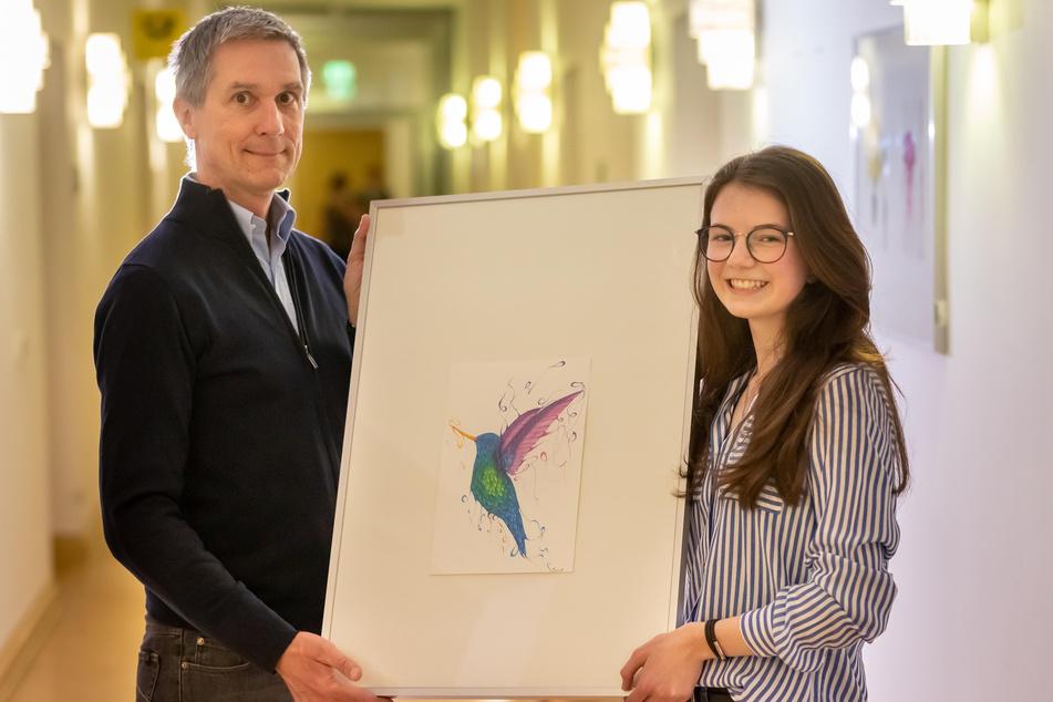 """Celina Stark (17) mit ihrem Bild """"Kolibri"""". Der kunstbegeisterte Richter Matthias Ries-Wolf (l.) steuerte für die 13 Bilder neun Rahmen bei."""