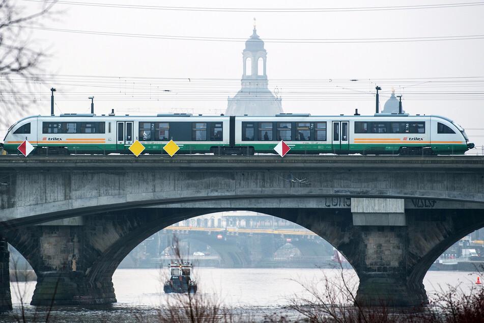 Ein Trilex-Zug der Länderbahn fährt am Morgen auf der Marienbrücke in Dresden über die Elbe.