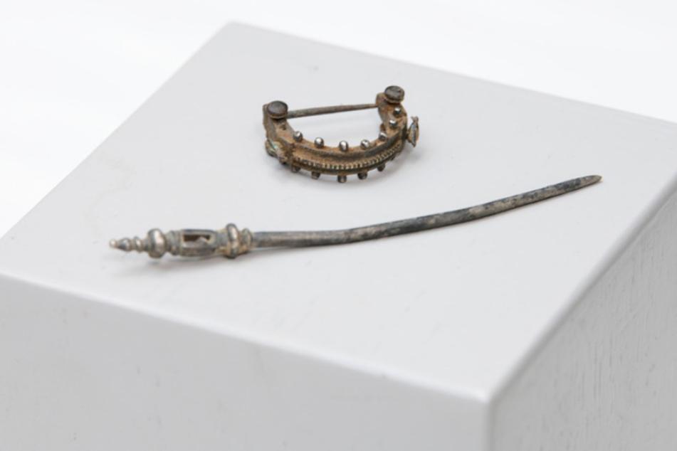 Besonders feine Stücke: Auf einem Sockel liegen eine Fibel (h) und eine Haarnadel.