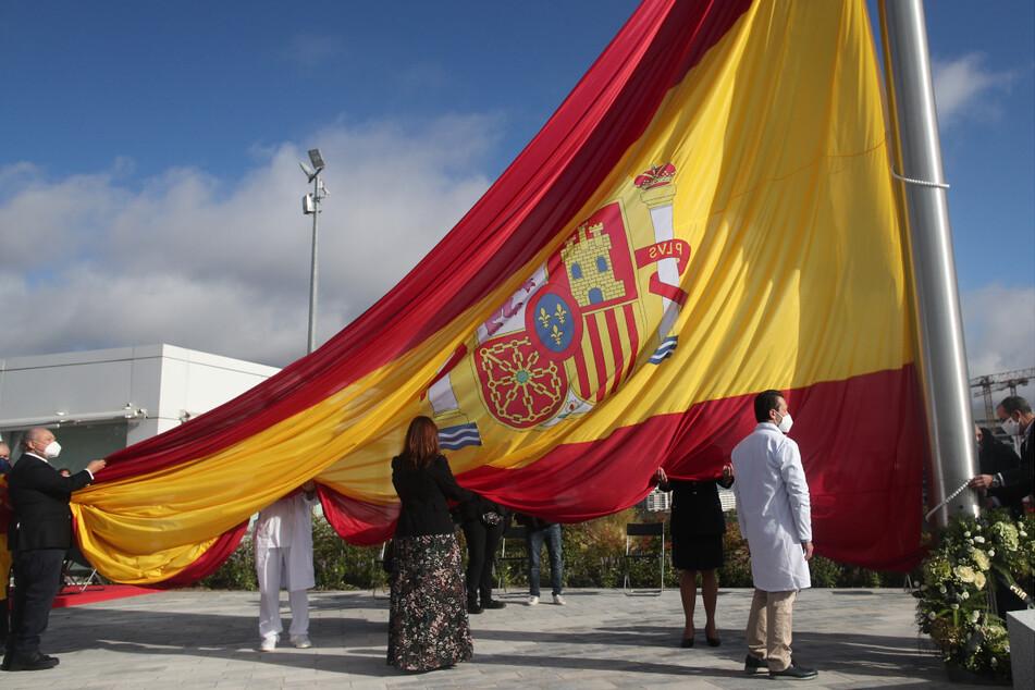 """Während der Ehrung der Bevölkerung von Madrid in ihrem Kampf gegen die Corona-Pandemie wird die Nationalflagge gehisst. Im spanischen Corona-Hotspot Madrid gilt ab dem heutigen Samstag nach dem Ende der zweiwöchigen Absperrung der Hauptstadt eine """"nächtliche Schließung"""" zwischen Mitternacht und 6 Uhr morgens."""