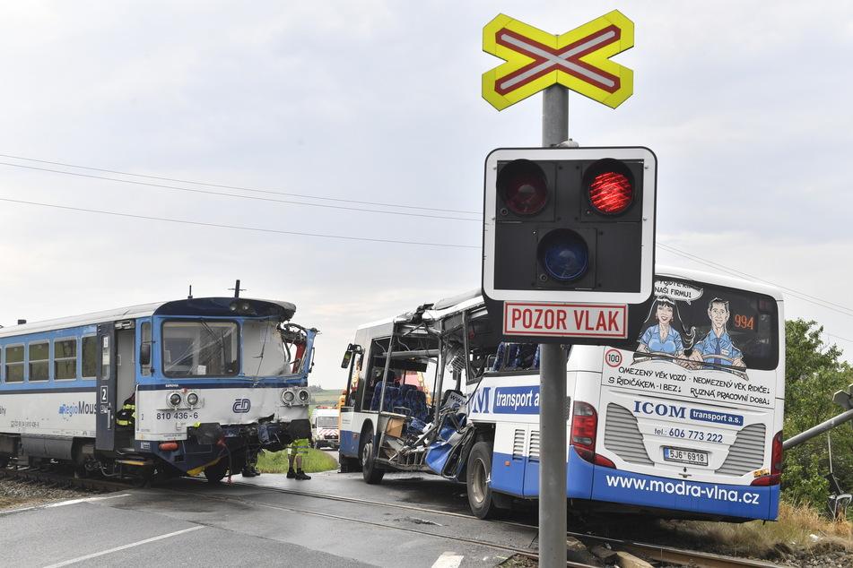 Ein beschädigter Bus und ein beschädigter Zug stehen an einem Bahnübergang. Beim Zusammenstoß eines Eisenbahntriebwagens mit einem Autobus sind in Tschechien zehn Menschen verletzt worden.
