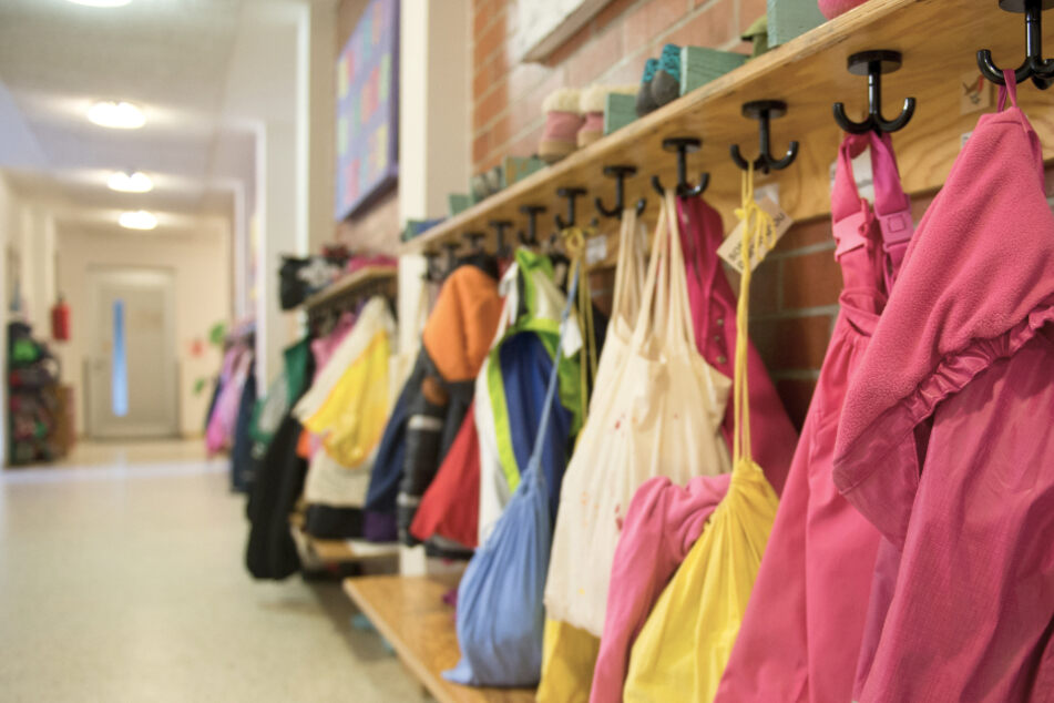 Jacken und Turnbeutel sind in einer Kindertagesstätte an einer Garderobe zu sehen.