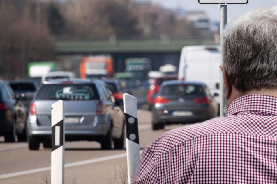 Mann fährt Tank leer und läuft dann mit Blumen über Autobahn