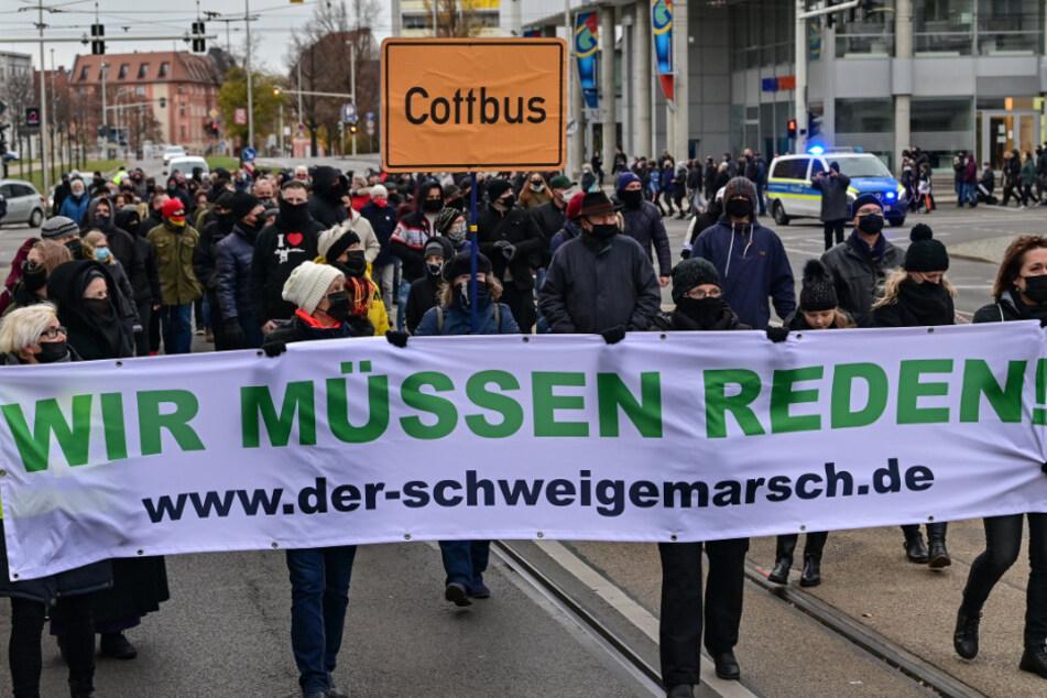 """Teilnehmer einer Demonstration gegen Corona-Maßnahmen tragen ein Transparent mit der Aufschrift """"Wir müssen reden!"""""""