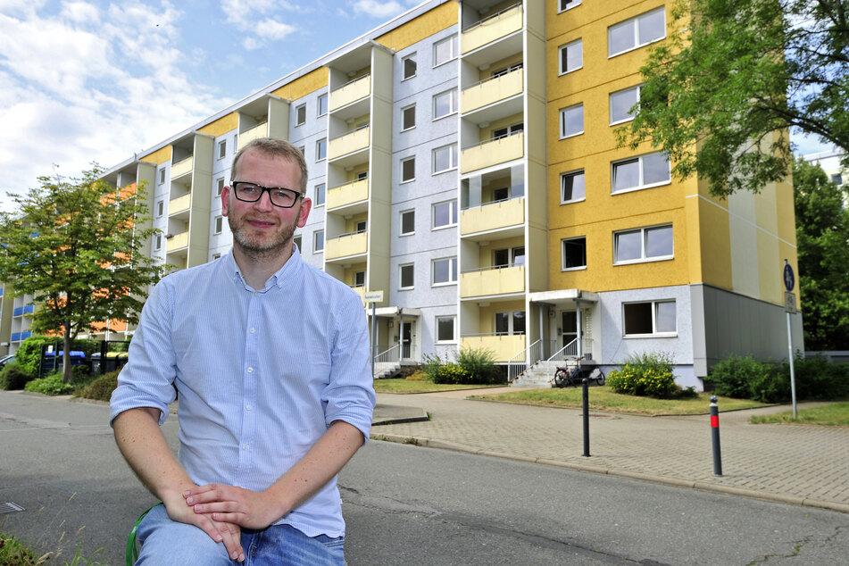 """Stadtteilmanager Thomas Rosner (36) sitzt vor dem Plattenbau, in dessen Erdgeschosswohnungen die """"Begehungen"""" stattfinden."""