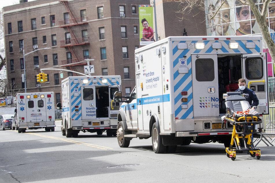 Krankenwagen stehen auf der Straße vor dem Elmhurst Hospital Center in New York.