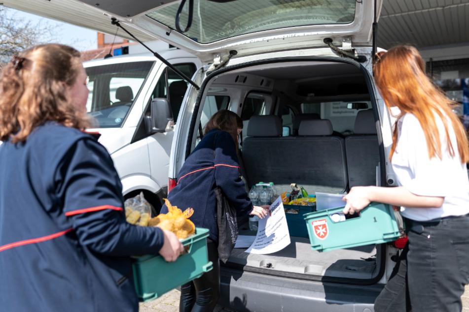 Mitarbeiter des Malteser Hilfsdiensts beladen ein Fahrzeug.