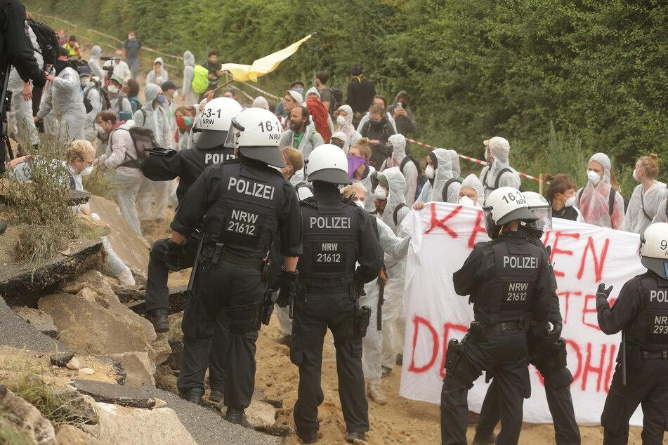 Keyenberg: Umweltaktivisten im weissen Overalls klettern über ein Wall um in dem Tagebau Garzweiler einzudringen und werden von der Polizei zuruckgewiesen.