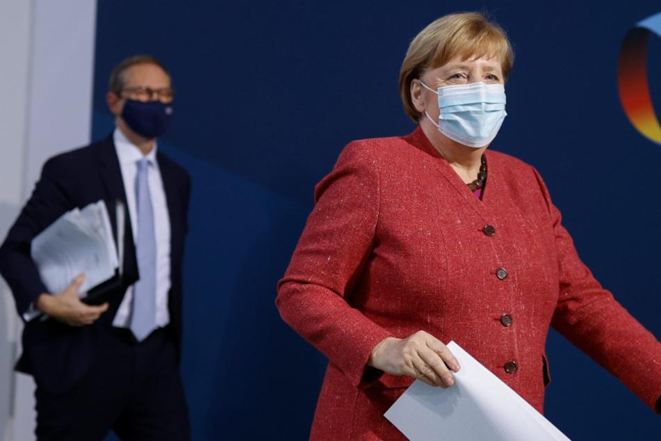 Bundeskanzlerin Angela Merkel (CDU, r) und Michael Müller (SPD), Regierender Bürgermeister von Berlin, verlassen nach einer Pressekonferenz einen Saal im Bundeskanzleramt.