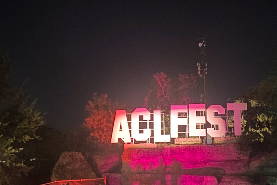 The ACL Fest sign is lit up atop the rocks in the middle of Zilker Park, creating the perfect photo op.