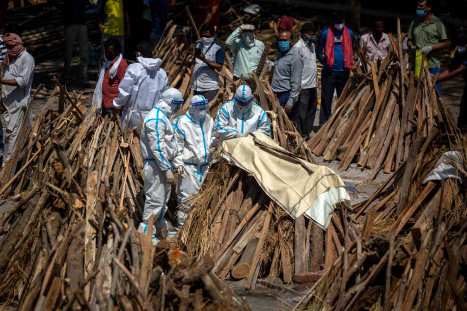 Neu-Delhi: Menschen vollziehen Rituale neben einem Scheiterhaufen für ein Familienmitglied, das an Covid-19 gestorben ist.