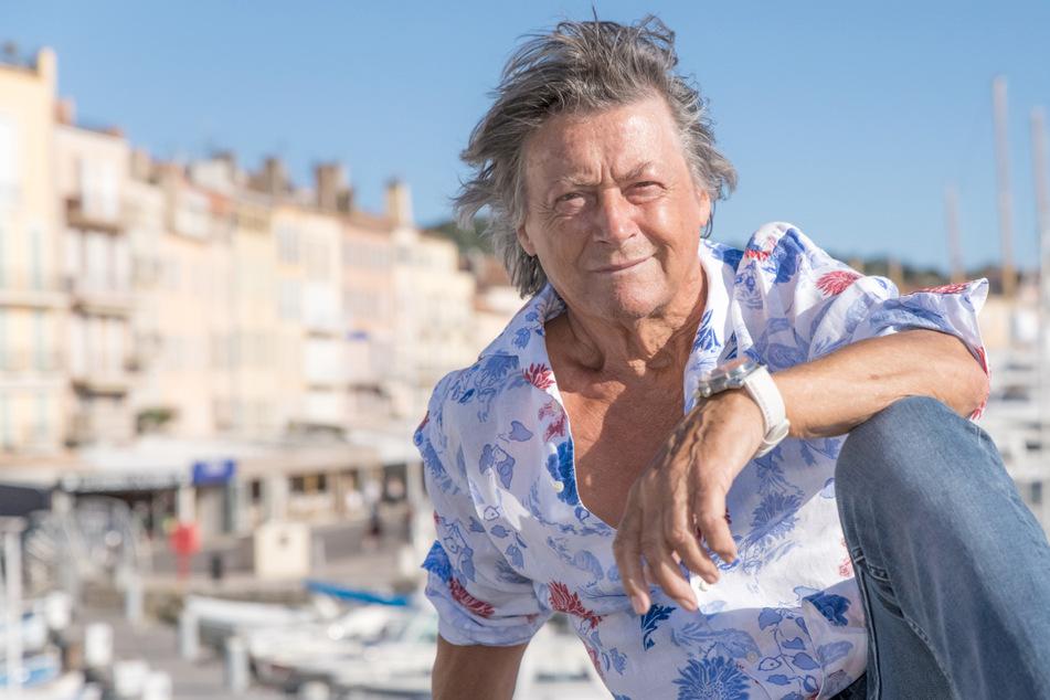 Schauspieler Herbert Herrmann (79) sitzt am Vieux port de Saint Tropez (Alter Hafen) auf einer Mauer.