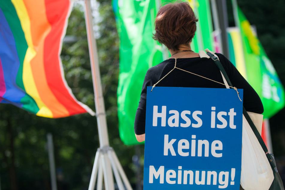 """Eine Aktivistin hat ein Plakat mit der Aufschrift """"Hass ist keine Meinung"""" über der Schulter. Gerade in der Pandemie haben Hass und Hetze zugenommen."""
