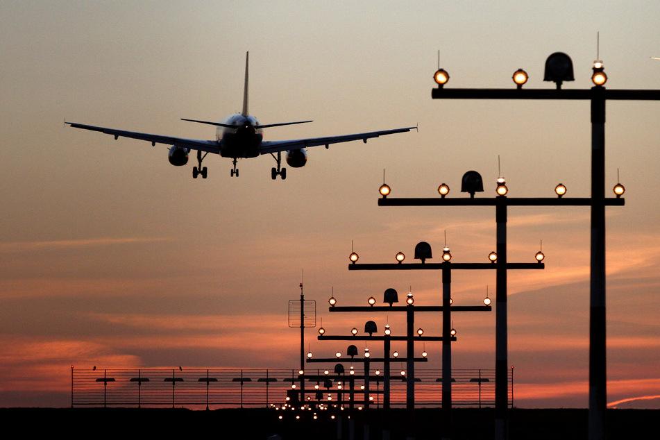 Ein Flugzeug ist während des Sonnenuntergangs im Landeanflug auf den Flughafen Düsseldorf.