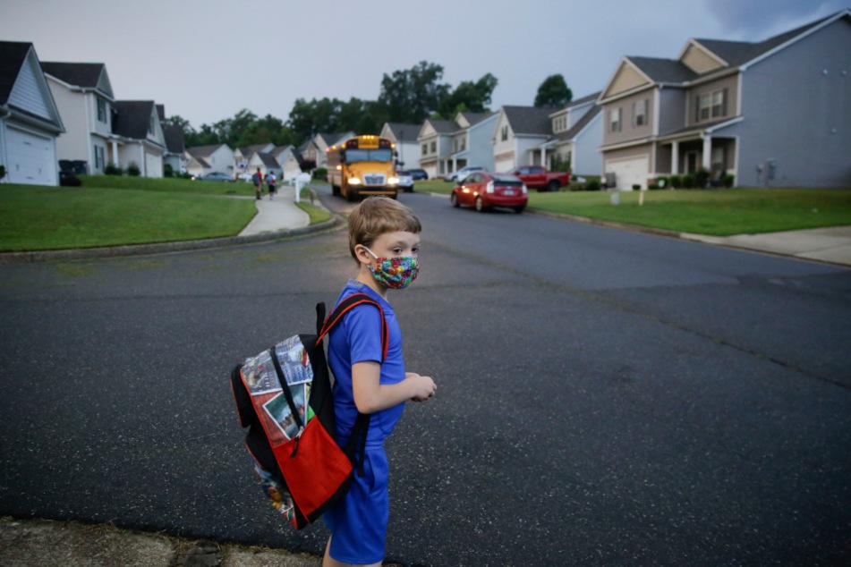USA, Dallas: Der 7-jährige Paul wartet am ersten Schultag auf den Schulbus. Zehntausende Schüler in Georgia und dem Rest des Landes kehren seit dem Lockdown im März erstmals wieder zurück zur Schule.
