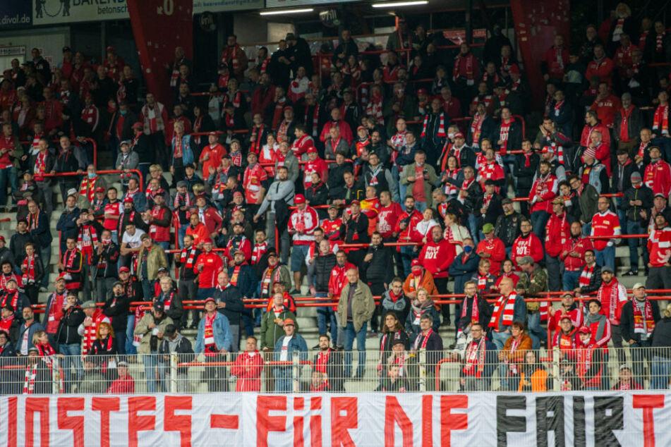 Fans von Union Berlin verfolgen das Spiel gegen Mainz 05 mit Abstand zueinander auf der Stehtribüne des Stadions.