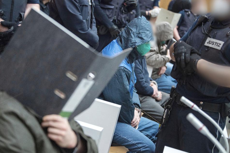 """Einige Angeklagte sitzen kurz vor Beginn des Prozesses gegen die rechtsterroristische Vereinigung """"Gruppe S."""" in einem Saal im Oberlandesgericht Stuttgart-Stammheim."""