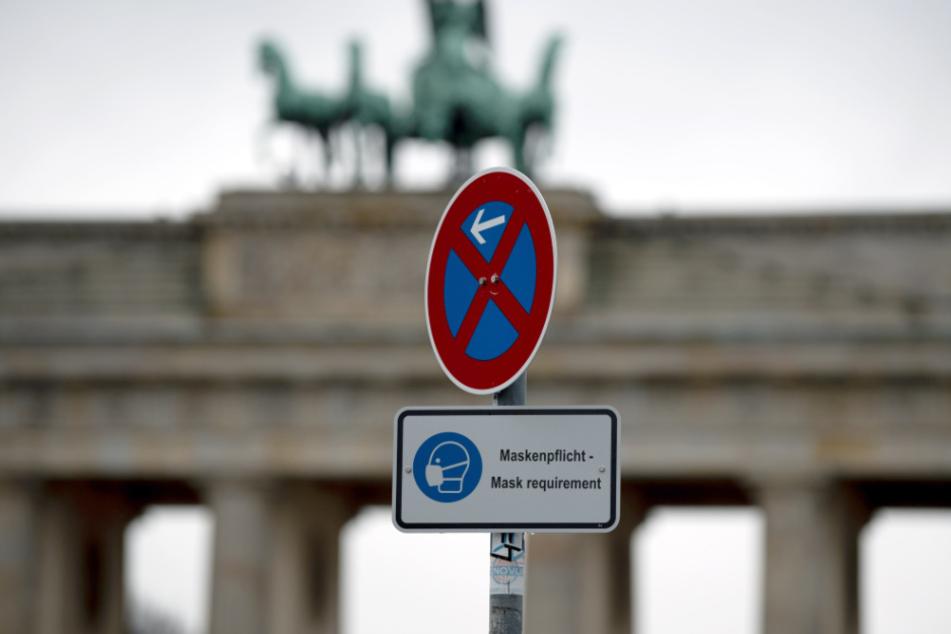 Ein Schild mit Hinweis auf die Maskenpflicht steht auf dem fast menschenleeren Platz vor dem Brandenburger Tor.