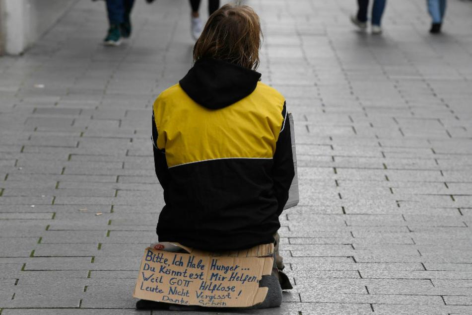 Eine Person sitzt mitten auf dem Bürgersteig und bittet um Almosen. Brandenburg gehört zu den fünf Ländern mit der geringsten Armutsdichte in Deutschland. (Symbolfoto)