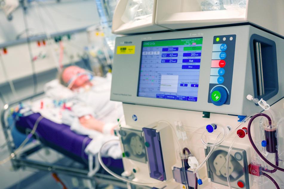 Ein Patient liegt während seines Aufenthalt im Krankenhaus Großhadern in einem Intensivzimmer an einem Beatmungsgerät und einem Dialysegerät (im Vordergrund).