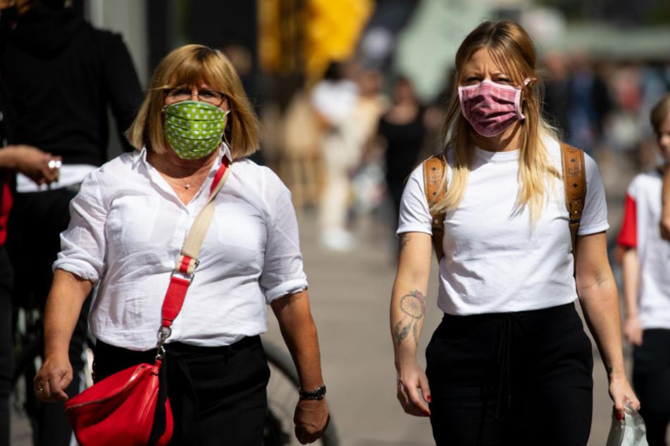 Mutter und Tochter (fast) im Partnerlook und beide mit selbst genähten Mundschutz-Masken beim Einkaufen unterwegs.