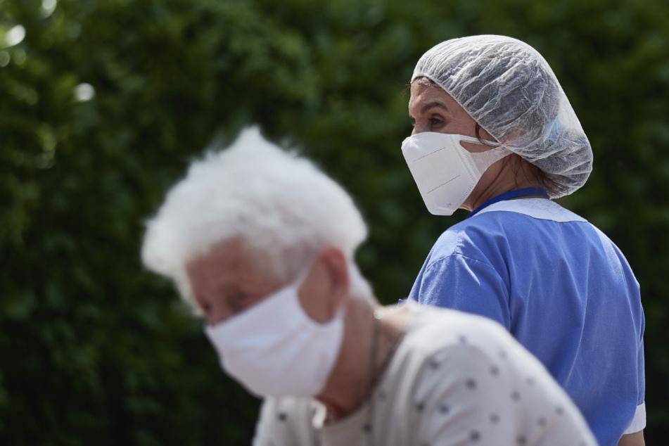 Eine Arbeiterin steht hinter einer Bewohnerin, die in sicherem Abstand mit ihren Familienangehörigen am Eingang eines Pflegeheims in Pamplona, Nordspanien, spricht.