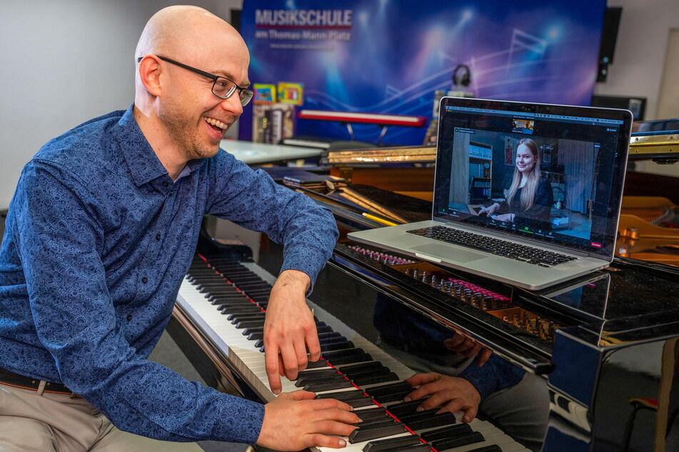 Musikpädagoge Patrick Schulze (40) schaut Luise Broszeit (22) beim Klavierunterricht mithilfe der Kamera auf die Finger.