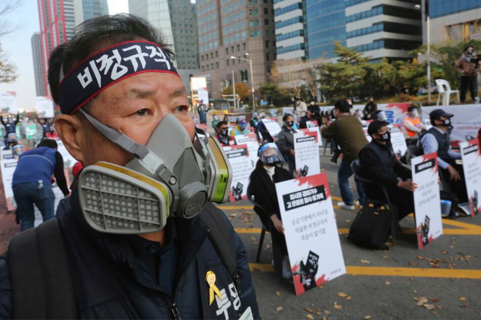 Seoul: Ein Mann mit Mund-Nasen-Schutz nimmt an einer Kundgebung teil, auf der Arbeiter für bessere Arbeitsbedingungen demonstrieren.