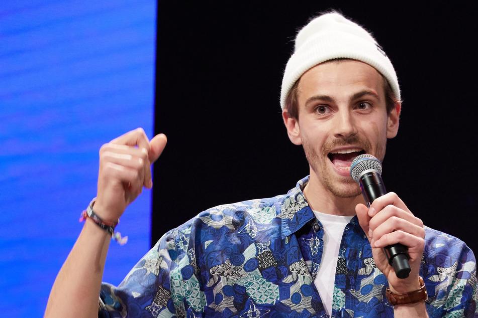 """Fynn Kliemann spricht auf einer Bühne auf der Marketing-Fachmesse """"Online Marketing Rockstars"""" (OMR) in den Messehallen."""