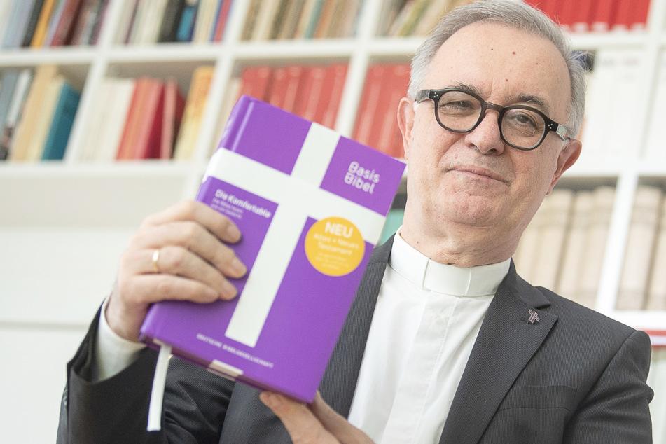 """Frank Otfried July (66), Landesbischof der Evangelischen Kirche in Württemberg, hält eine Ausgabe der """"BasisBibel"""" in der Hand."""