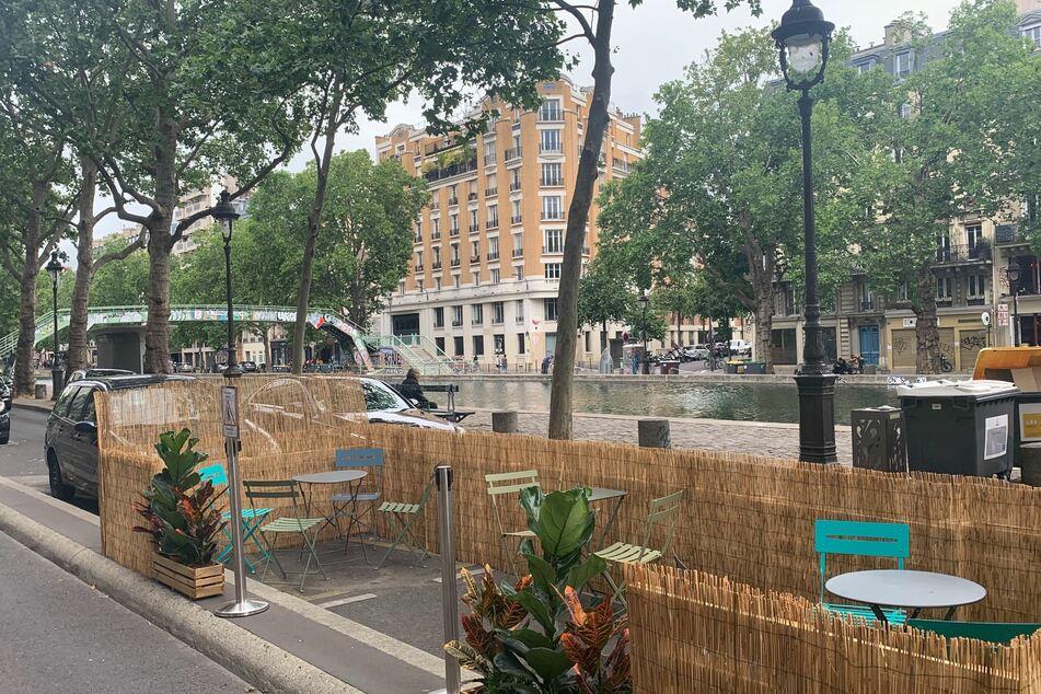 Ein Restaurant am Quai de Valmy am Canal Saint-Martin mit seiner neuen Terasse, die auf die Straße erweitert und mit einem Strohzaun abgegrenzt worden ist.