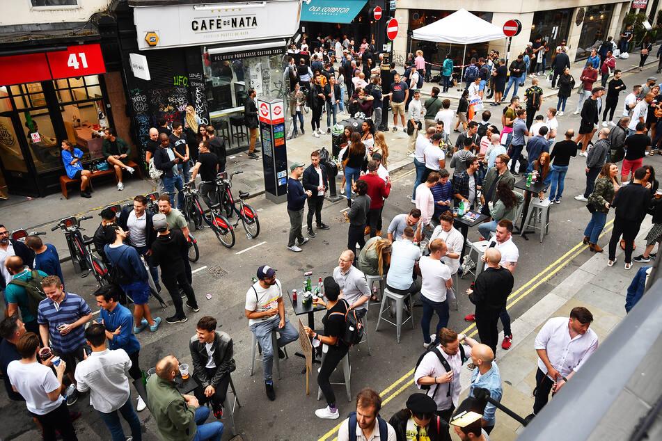 Menschen versammeln sich zum gemeinsamen Trinken auf einer Straße vor Bars im Stadtteil Soho. Pubs waren in England für über drei Monate geschlossen.