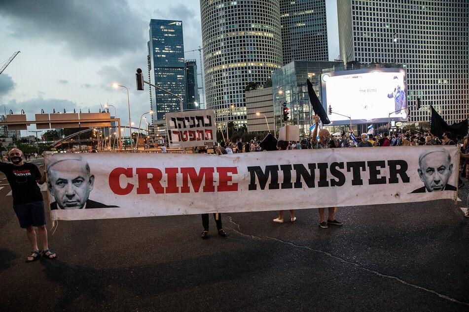 """Aktivisten einer Anti-Korruptionsbewegung halten ein Banner mit der Aufschrift """"Verbrechensminister"""", während eines Protests gegen die neuen Gesetze, die von der Regierung des israelischen Premierministers Netanjahu durchgesetzt werden."""