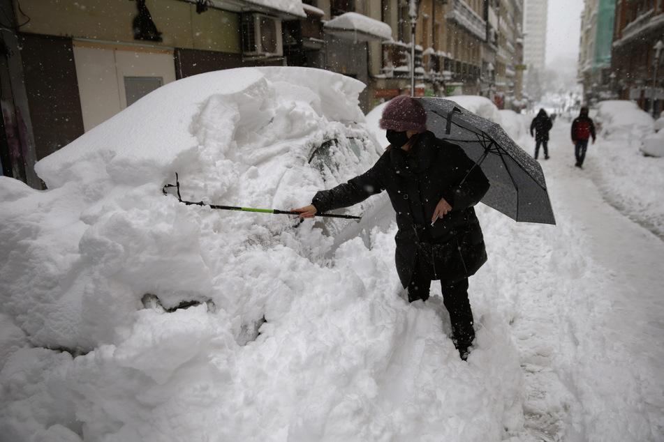 Eine Frau in Madrid befreit ihr Auto von einer hohen Schneeschicht. Laut des Wetterdienstes AEMET gab es solch einen Schneefall das letzte Mal im Februar 1984.