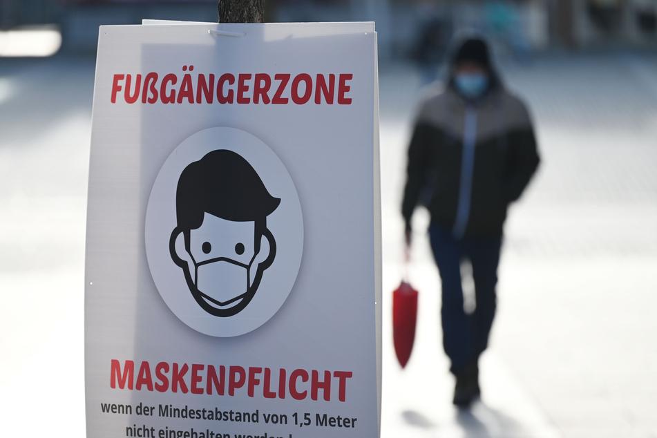 Ein Bild weist auf die Maskenpflicht in einer Fußgängerzone hin. (Archivfoto)