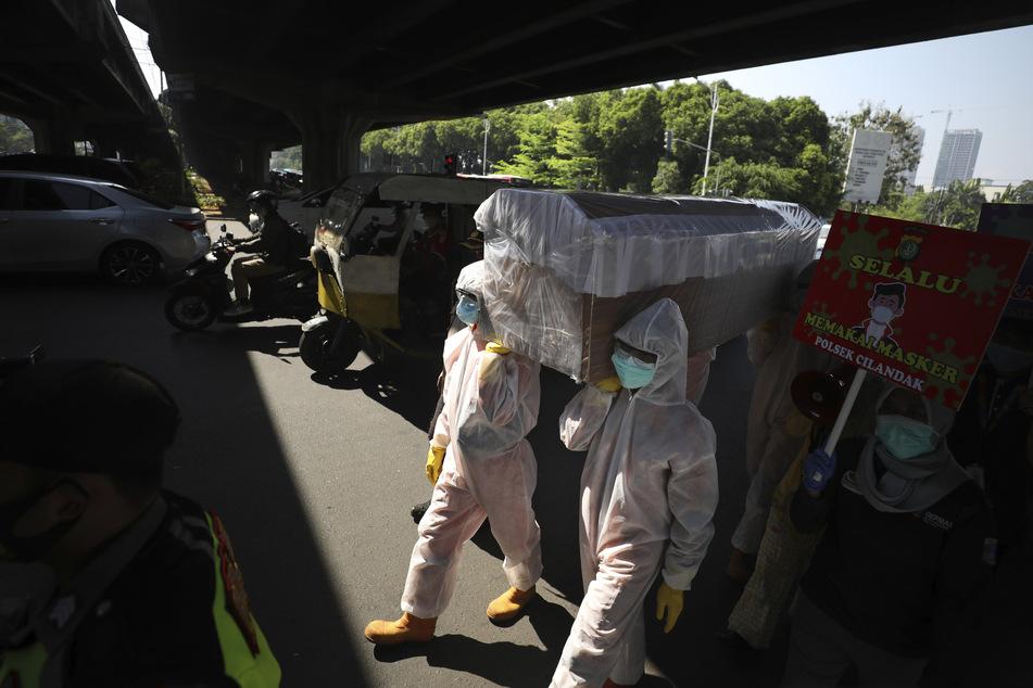 Regierungsbeamte in Schutzanzügen tragen einen Schein-Sarg bei einer Aufklärungskampagne um die Menschen daran zu erinnern, stets die Gesundheits- und Sicherheitsprotokolle zu befolgen, um die Ausbreitung der Corona-Pandemie einzudämmen.