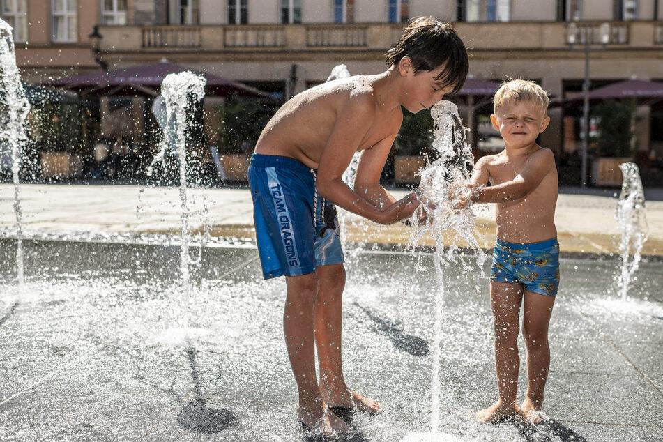 Hier werden Kinder tüchtig gewässert: Benn (8) und Finn (4) genießen das Wasserspiel am Jacobispielplatz.