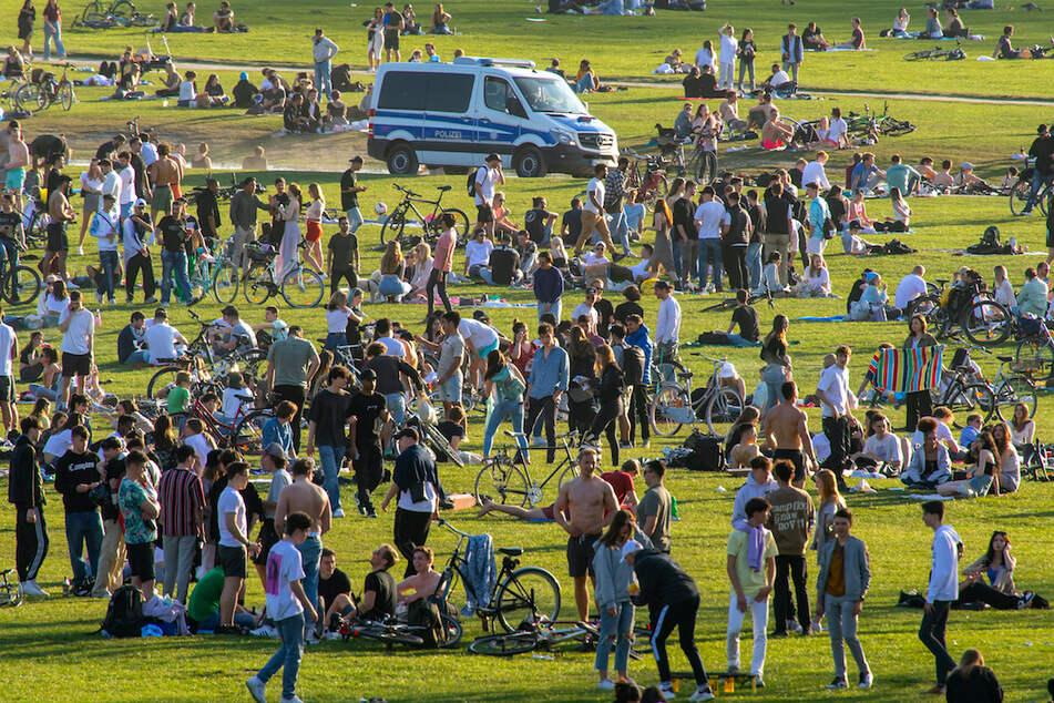 Polizisten fahren Streife im Englischen Garten, wo Hunderte von Menschen auf der großen Wiese nahe dem Monopteros den sonnigen Frühlingstag mit warmen Temperaturen verbringen.