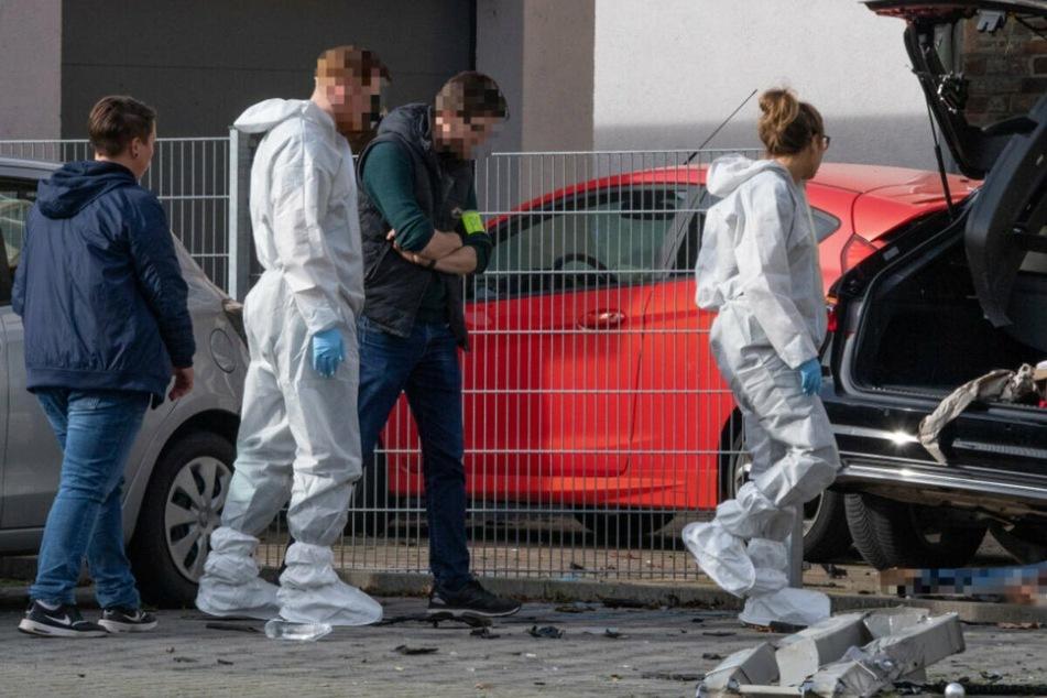 Mitarbeiter der Spurensicherung stehen in Limburg an dem Wrack eines dunklen Autos, unter dem die Leiche einer Frau liegt.