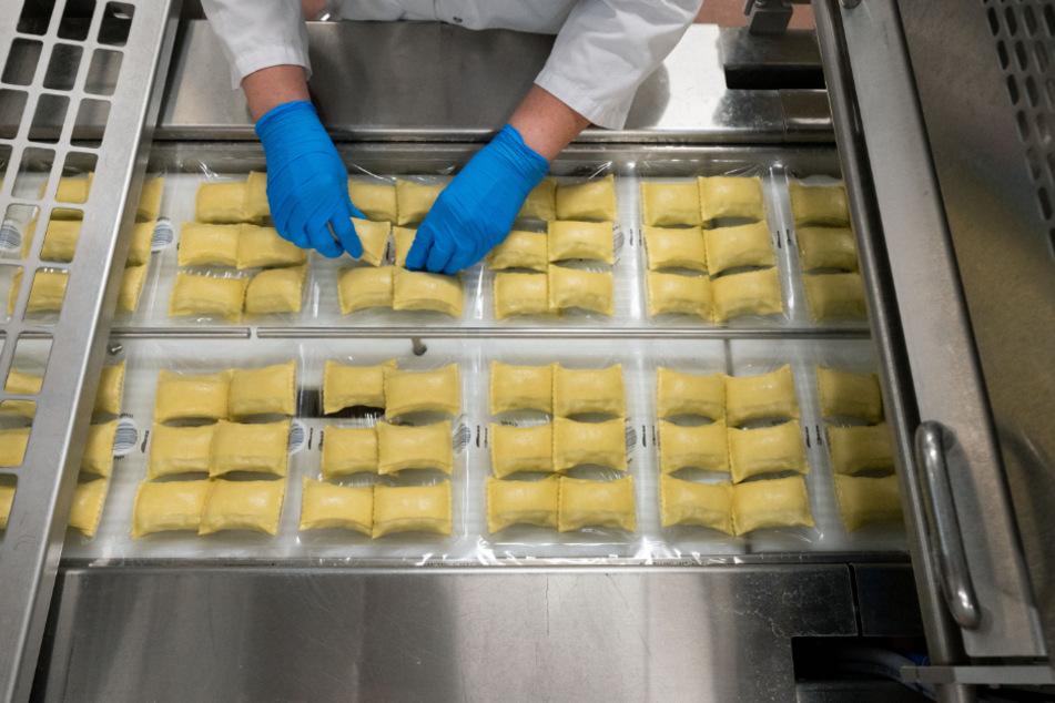 Eine Mitarbeierin des Teigwarenproduzenten Bürger GmbH & Co. KG richtet Maultaschen in der Verpackung aus.