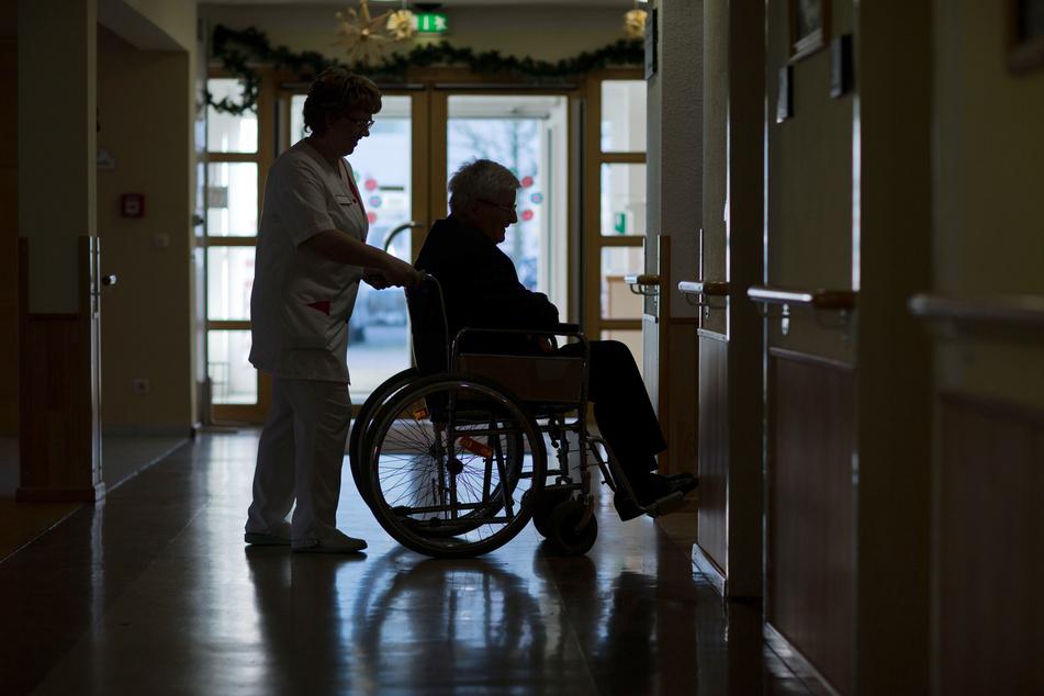 Ein Bewohner eines Pflegeheimes in Parchim wird mit seinem Rollstuhl über den Flur geschoben.