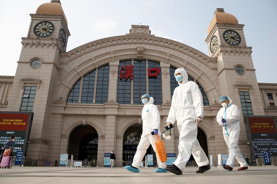 Arbeiter in Schutzanzügen laufen am Bahnhof Hankou in Wuhan vorbei.