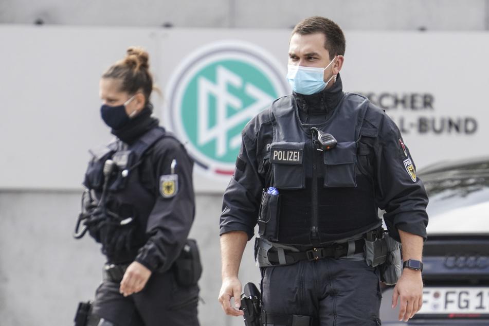 Polizisten gehen vor der Zentrale des Deutschen Fußball-Bundes (DFB) zu ihren Fahrzeugen.