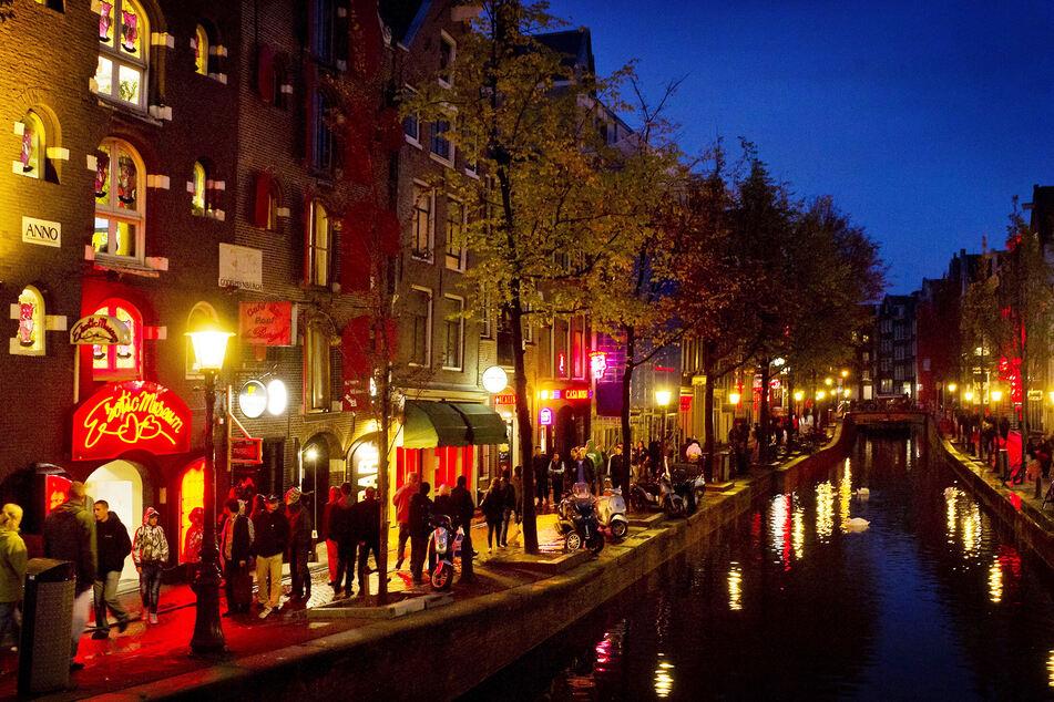 Menschen schlendern am Abend an einer Gracht entlang durch den Rotlichtbezirk De Wallen. Das Amsterdamer Rotlichtviertel wurde für Fußgänger zur Einbahnstraße erklärt.
