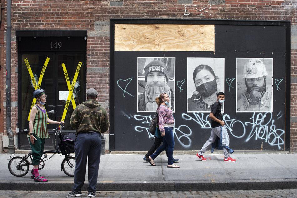 Passanten, die zur Vermeidung einer Verbreitung von Covid-19 Mundschutze tragen, gehen im Stadtteil SoHo an bei Protesten zerstörten und mit Holz bedeckten Fenstern vorbei, auf denen Porträts von systemrelevanten Arbeitern während der Corona-Pandemie angebracht sind.
