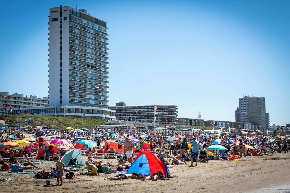 Zahlreiche Menschen genießen das heiße Wetter am Strand nahe dem Bahnhof Zandvoort.