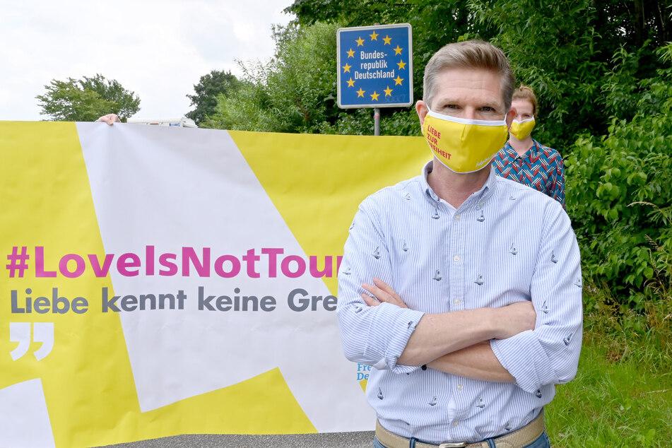 Mit einer Schutzmaske steht Heiner Garg, FDP-Landesvorsitzender und Gesundheitsminister von Schleswig-Holstein, bei einer Demonstration am Grenzübergang Padborg.