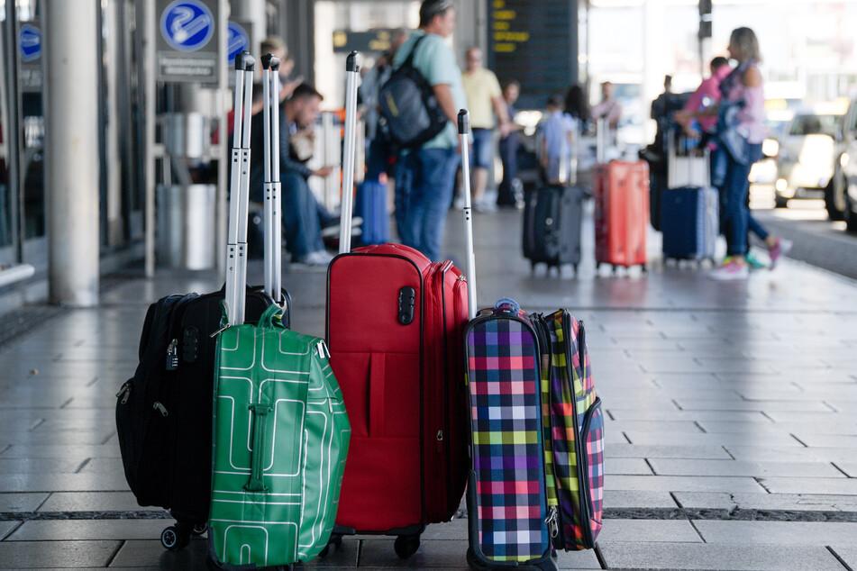 Hamburg: Fluggäste warten am Eingang zum Helmut-Schmidt-Airport neben ihrem Gepäck.