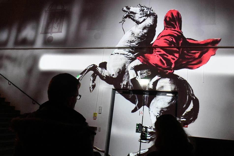 """Besucher betrachten in der Ausstellung """"The Mystery of Banksy – A Genius Mind"""" bei einem Presserundgang eine Videoprojektion."""
