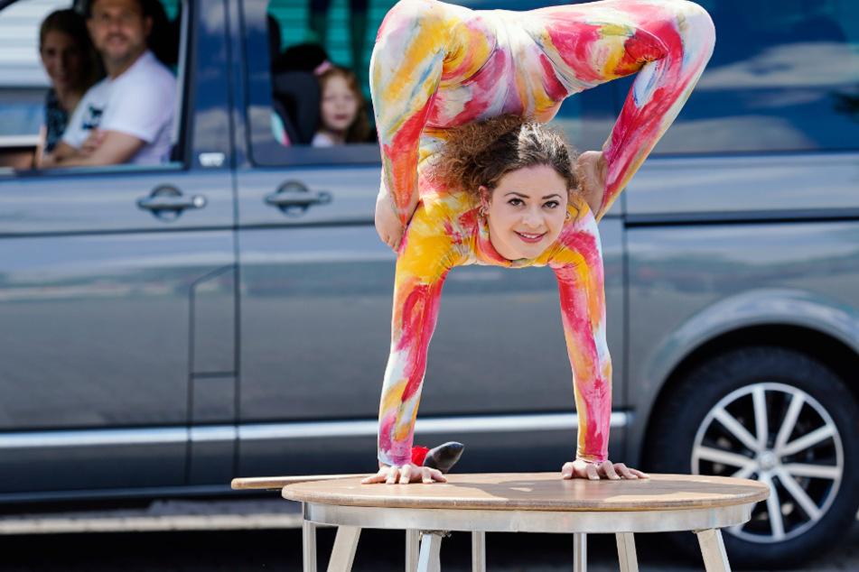 """Eine Zirkuskünstlerin zeigt Kunststücke bei einem Zirkus-Drive-In des Kinder- und Jugendzirkus """"Paletti""""."""
